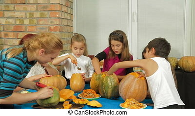 Group of Children Carving Halloween Pumpkins - Two adults...