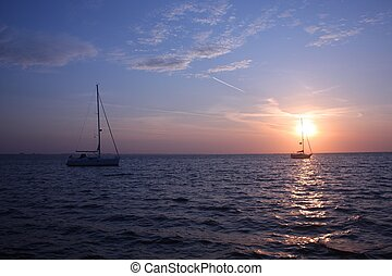 yachts at anchor in studland bay with sunrise in the...
