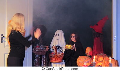 After Trick-Or-Treat - Woman ways good-bye to children in...