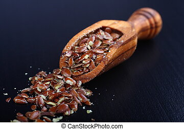 Broken flax seeds in wooden scoops on black background -...