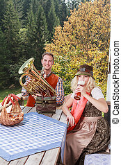 Young couple in traditional Bavarian clothes in common enjoy...
