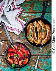 fried sausages with apples, onions and rosemary in a frying...