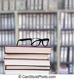 glasses with books - glasses above the stacked books,...