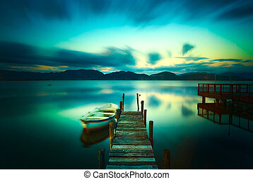 Wooden pier or jetty and a boat on a lake sunset. Versilia...