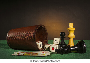 Dice Cup with Deck Cards and Chess Pieces on Green