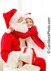 smiling girl with santa claus and gift at home - holidays,...