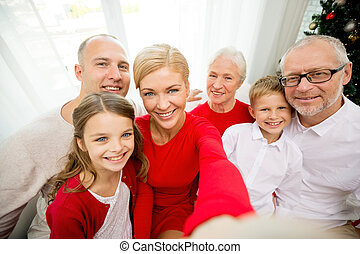 smiling family making selfie at home - family, holidays,...