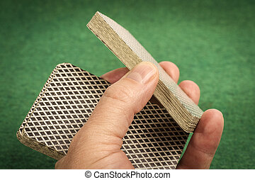 Hand wiht Deck of Cards on Green