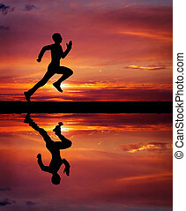 Silhouette of running man on sunset fiery background. Silhouette