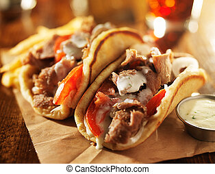 greek gyros with tzatziki sauce and fries close up