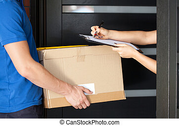 Woman signing parcel delivery papers - Delivery guy holding...