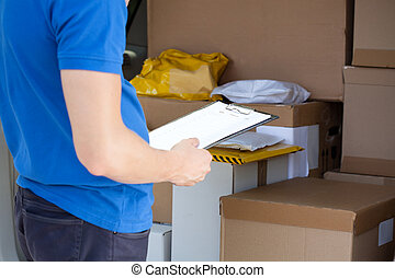 Checking van full of parcels - Delivery man checking...