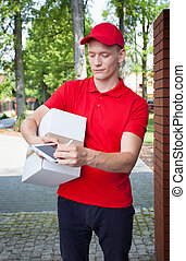Delivery man with a tablet - Delivery man carrying a box and...