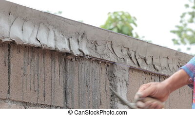 Worker plastering concrete at wall of house construction