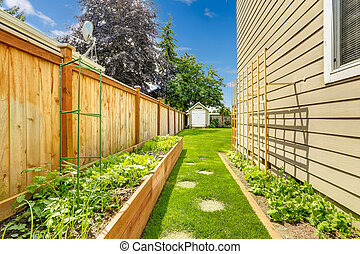 Fenced backyard with garden bed and green lawn