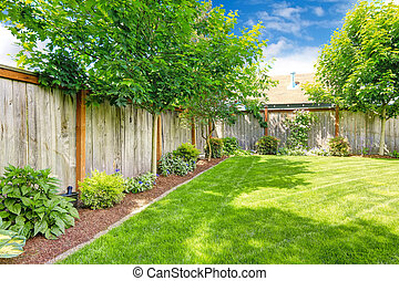 Fenced backyard with lawn and flower bed - Backyard with...