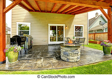 Patio area with tile floor and stone trimmed fire pit -...