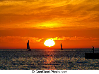 sailboat silhouettes at sunset