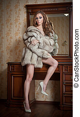 Attractive sexy young woman wearing only a fur coat posing...