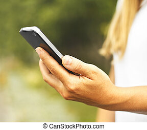 Woman hand using a smart phone on the street