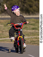 Girl riding her bike and giving the two finger solute