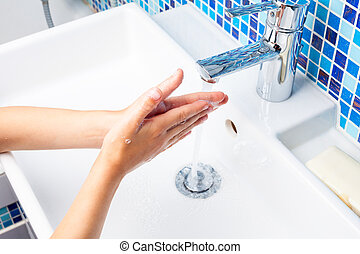 Child washing hands - Girl washing her hands with soap in a...