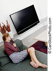 woman watching television a - young woman sitting in sofa...