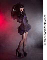 Gothic Lolita girl with lace umbrella, studio shot on black...