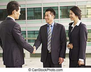 asian businesspeople shaking hands and smiling