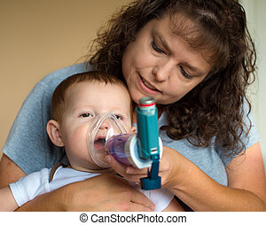 Infant getting breathing treatment from mother while...