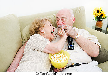 Seniors Popcorn Television - Senior woman laughs and feeds...