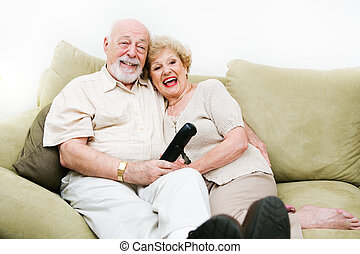 Seniors Enjoying Television - Senior couple relaxing at home...