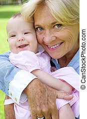 Grandmother and grandchild smiling - Close up portrait of a...