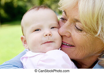 Senior woman holding cute baby - Close up portrait of a...
