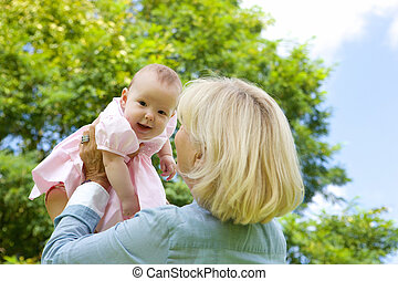 Drandmother lifting grandchild up - Close up portrait of a...