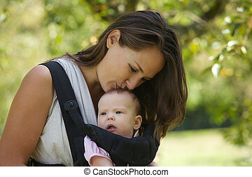 Beautiful mother kissing cute baby on the head