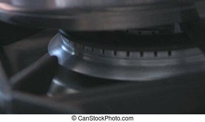 Blue gass flame lit under a pan