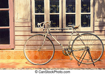 vintage bicycle leaning against  house wall