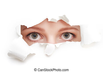 eyes of woman peeking through a hole torn in white paper...