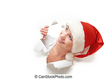 happy woman with christmas hat peeking through a hole torn...
