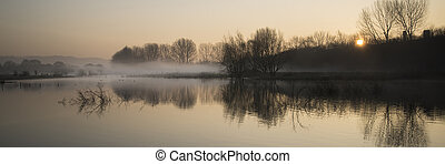Panorama landscape of lake in mist with sun glow at sunrise...