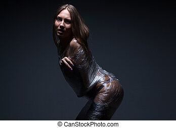 Photo of young wraped woman on black background