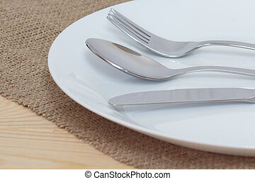 Fork, knife and spoon on white glass plate