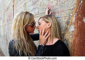Women - two beautiful Young women flirting. rusty concrete...