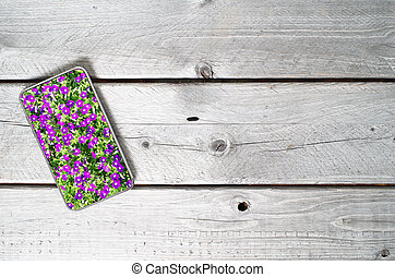 Modern mobile device showing violet flowers on top of an old...
