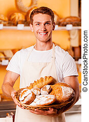 Proud of his baked goods Handsome young man in apron holding...