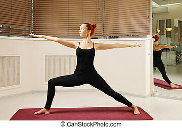 Yoga pose arms stretched - Redhead woman in yoga pose...