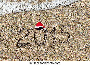 happy new year 2015 with christmas hat on sandy beach -...