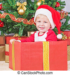 Smiling child with santa hat in gift box against christmas tree