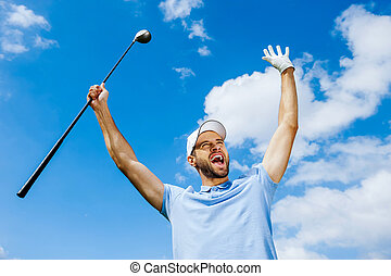 I won! Low angle view of young happy golfer holding driver...